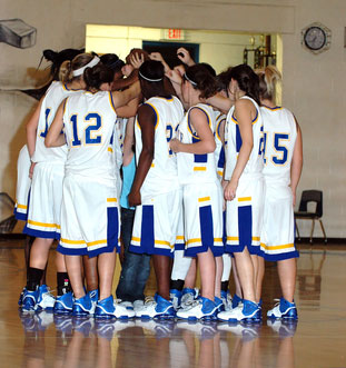 teen girls in basketball huddle in gymnasiumn