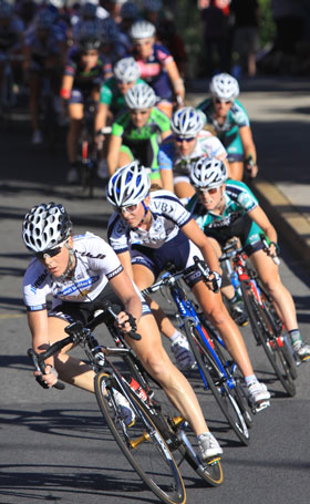 pack of female cyclists round a corner in race