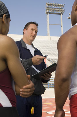coach talking with 2 football players